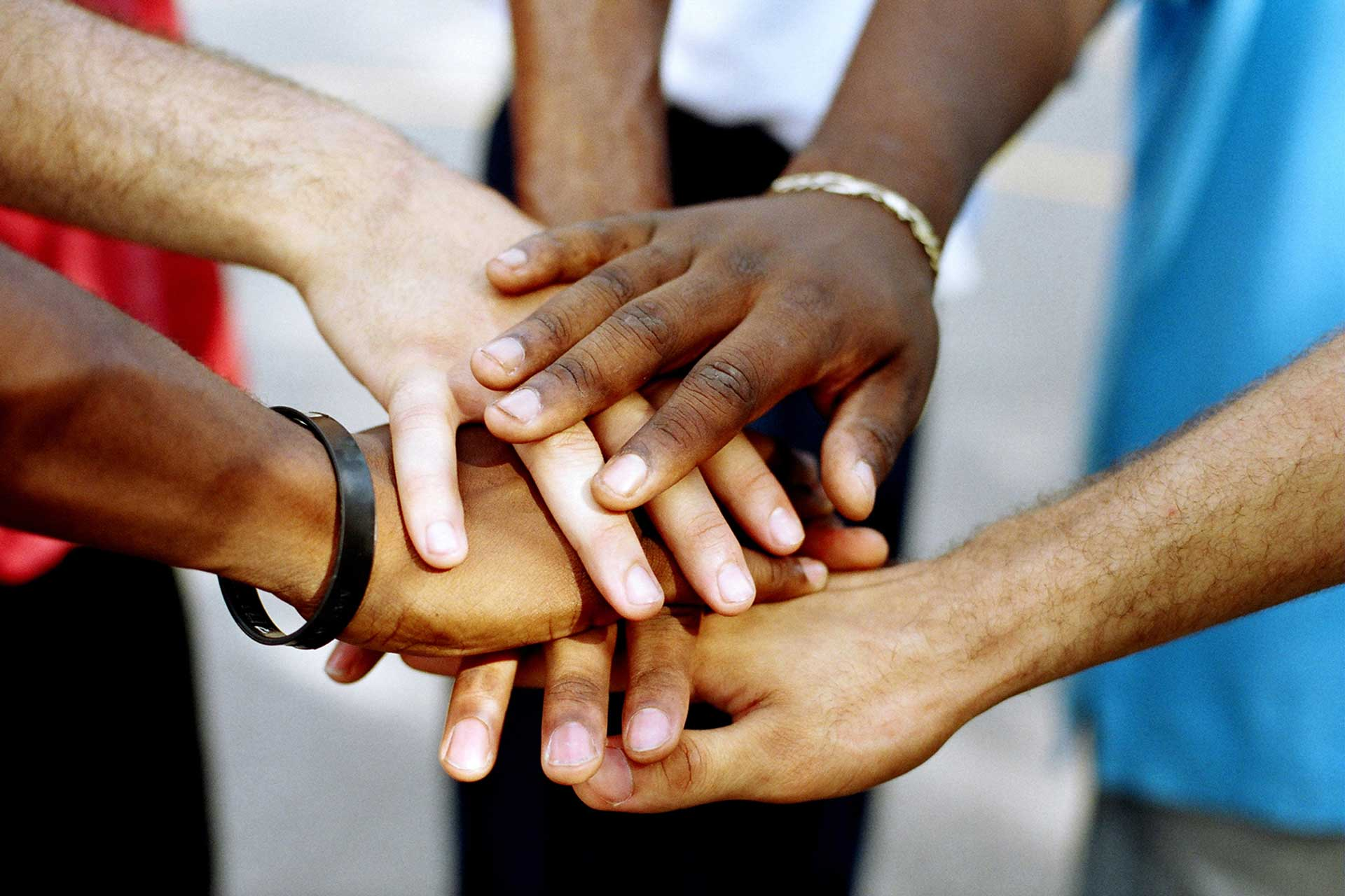 Circle of hands of all races coming together for a picture
